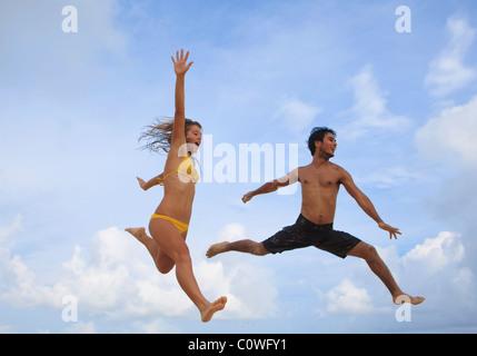 junges Paar springen in der Luft am Strand von hawaii - Stockfoto