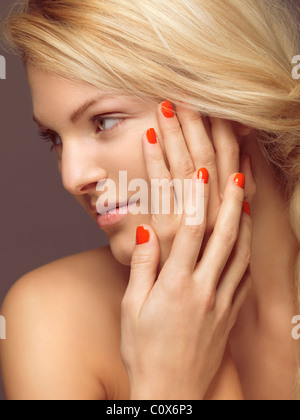 Schönheit-Porträt einer jungen Frau mit leuchtend orangefarbenen Nagellack