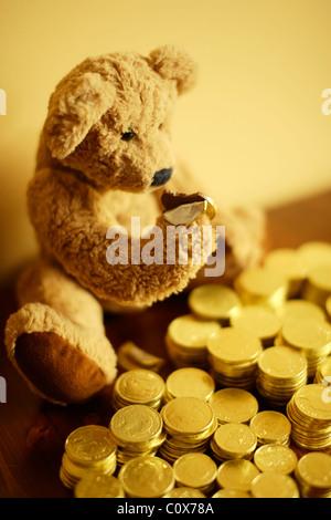 Ted steckt in seiner Schokolade Goldmünze Investition. - Stockfoto