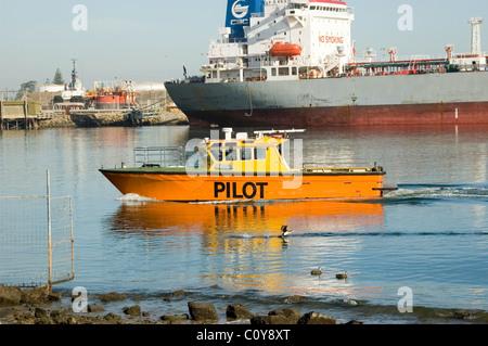 Ein Pilot Boot ans Ufer, großes Frachtschiff im Hintergrund, Port Adelaide, South Australia. - Stockfoto
