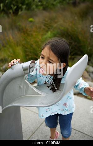 Mädchen-Getränke von Wasser-Brunnen - Stockfoto
