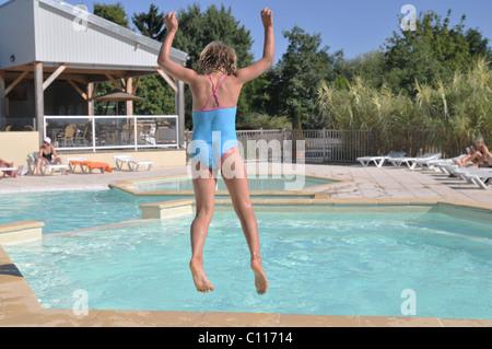 Mädchen Sprung ins Schwimmbad im Urlaub - Stockfoto