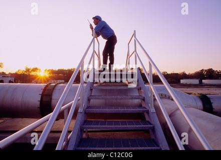 Ingenieur auf ein Walkie Talkie Funkgerät bei Sonnenuntergang auf einer Kläranlage, Houston, Texas, USA - Stockfoto