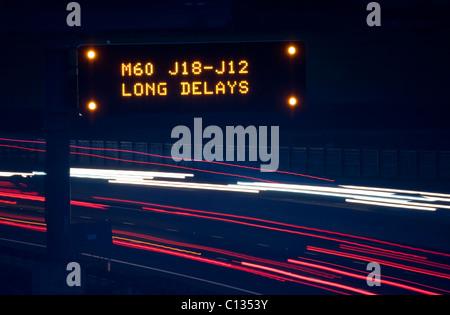 Scheinwerfer wegen des Verkehrs auf der Autobahn A1/M Weitergabe Gantry Warnsignal für Verzögerungen die M60 voraus - Stockfoto