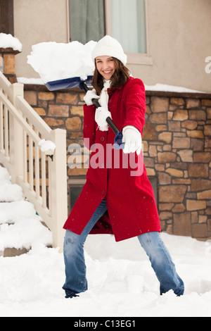 USA, Utah, Lehi, Porträt der jungen Frau werfen Schnee Schnee Schaufeln - Stockfoto