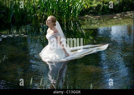 Frau Dame zu Fuß ins Wasser des Sees bis zur Taille in langen Brautkleid mit Seerosen und Schilf - Stockfoto
