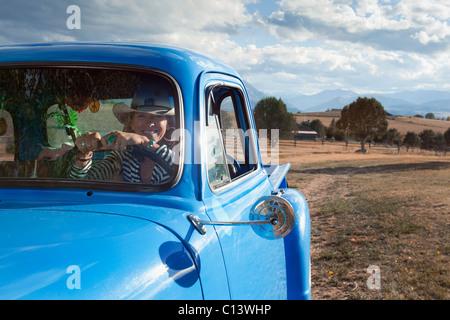 USA, Colorado, Carbondale, Cowgirl treibende alte altmodische Pickup-Truck im Feld - Stockfoto