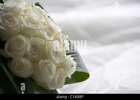 Brautstrauß aus weißen Rosen liegen auf einem weißen Hintergrund - Stockfoto