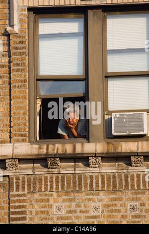 African American Woman Blick Fenster der Wohnung in New York City. - Stockfoto