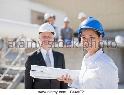 Geschäftsfrau hält Blaupausen stehend mit Kollegen - Stockfoto