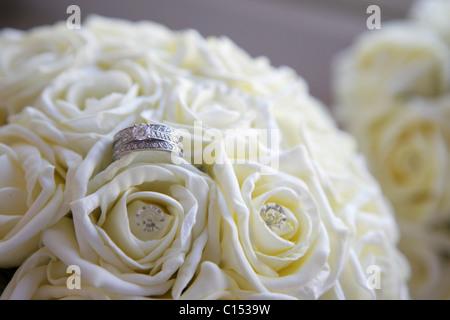 Diamant-Verlobungsring in eine Hochzeit Blume Bouquet aus weißen Rosen - Stockfoto