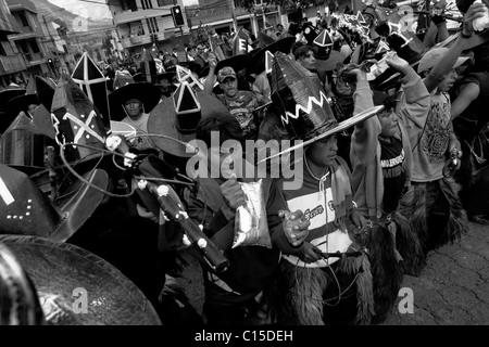 Indianer, tragen schwarze Hüte aus Karton, tanzen und schreien wütend während das Inti Raymi fest in Cotacachi, - Stockfoto