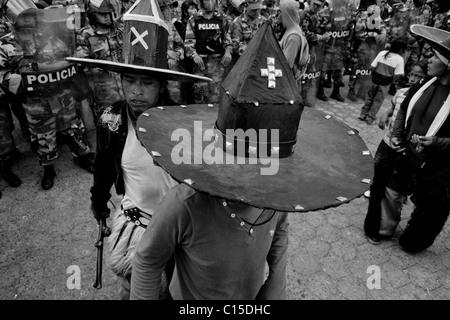 Indianer, Karton Hüte tragen tanzen vor dem Polizei-Block während das Inti Raymi fest in Cotacachi, Ecuador. - Stockfoto