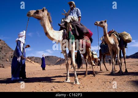 Touristen, die Kamele reiten geleitet von Tuareg-Männer auf einer Wanderung durch die Sahara Wüste, Libyen, Nordafrika - Stockfoto