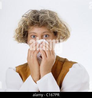 Eine blonde Frau bläst ihre Nase mit einem Papiertaschentuch - Stockfoto