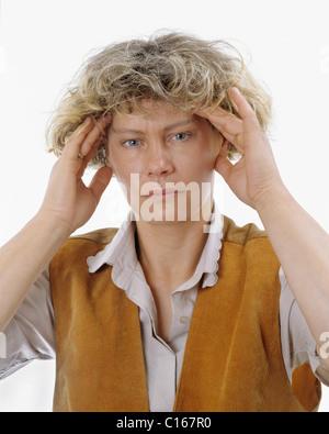 Eine blonde Frau hält ihren Kopf mit Händen, starke Kopfschmerzen, Migräne, Überlastung - Stockfoto