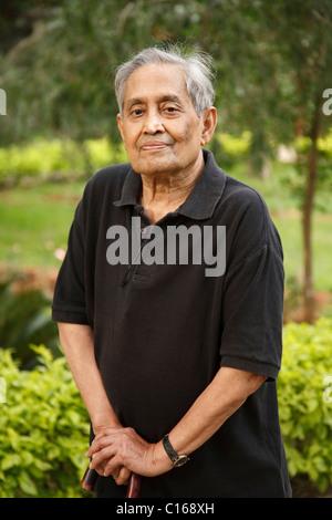 Alte indische asiatischer Mann steht in einem Park mit einem Gehstock - Stockfoto