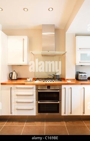 Moderne weiße Küche mit Holz Arbeitsplatten und Geräten aus rostfreiem Stahl - Stockfoto