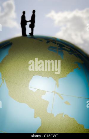 Spielfiguren schütteln Hände auf einem bunten Glas-Globus in einem internationalen Geschäft Konzept Bild. - Stockfoto