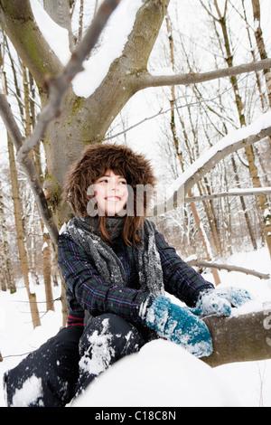 Mädchen sitzen unter schneebedeckten Baum - Stockfoto