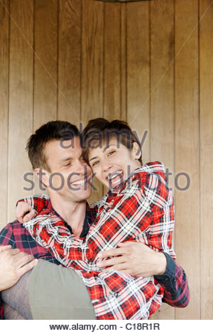 Mann trägt Frau in der Hütte im park - Stockfoto
