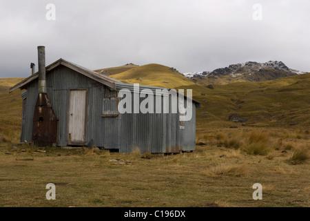 Verlassene Wellblech Hütte in einer hügeligen Landschaft, Nevis überqueren, Cromwell, Otago, Südinsel, Neuseeland - Stockfoto