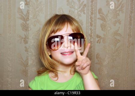 kleine Mädchen lustige Sonnenbrillen Retrotapeten Sieg Geste die Hand - Stockfoto