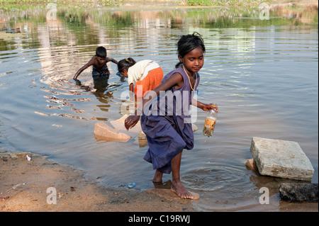 Armen indischen niedrigere Kaste Kinder Angeln mit Sari und setzen in einer Plastikflasche in den Fluss. Andhra - Stockfoto
