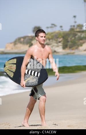Junger Mann mit Surfbrett am Strand - Stockfoto