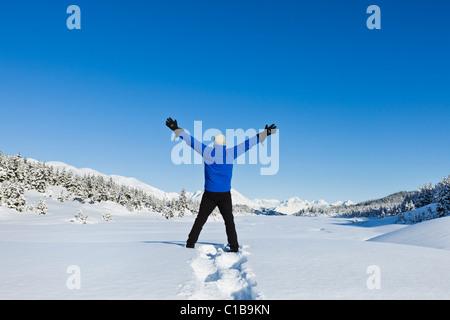 Ein männlicher Wanderer auf Schneeschuhen in Alaska hält seine Arme ausgestreckt mit dem Ausdruck ihrer Freude an - Stockfoto