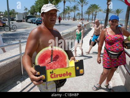 Mann, die Wassermelone in Playa de Plalma Arenal Strand Mallorca Spanien zu verkaufen - Stockfoto
