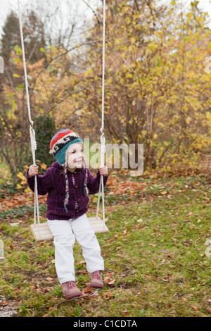 Kleines Mädchen auf einer Schaukel im Garten - Stockfoto