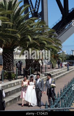 Asiatische Hochzeitsgesellschaft am Fuße des Sydney Harbour Bridge Walk haben ihre Fotos gemacht, NSW, Australien - Stockfoto
