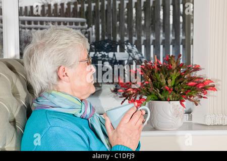 Deprimiert senior Frau alleine halten heißes Getränk traurig und einsam durch ein Fenster auf Schnee mit Weihnachten - Stockfoto