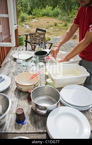 Mann beim Abwasch im Freien im Sommer. - Stockfoto