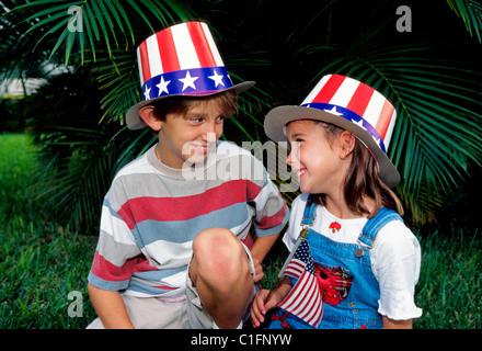 Ein junger Bruder und Schwester in patriotischen Uncle Sam Hüte anzeigen Geschwisterliebe während einer Independence - Stockfoto