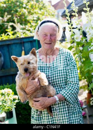 Porträt von senior Frau Holding Hund im Garten - Stockfoto
