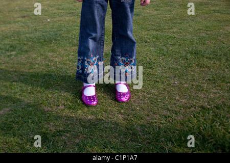 junge Mädchen tragen Jeans und rosa Schuhe steht auf dem grünen Rasen im park - Stockfoto
