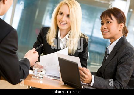 Zwei intelligente Damen hören Erklärung von ihrem Chef mit Liebe - Stockfoto