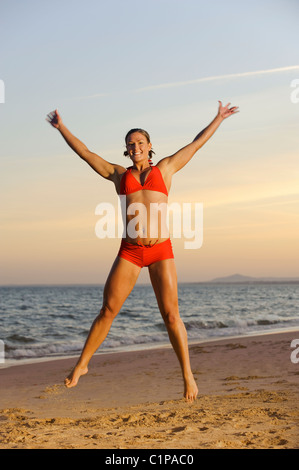 Junge Frau mit Bikini am Strand springen - Stockfoto
