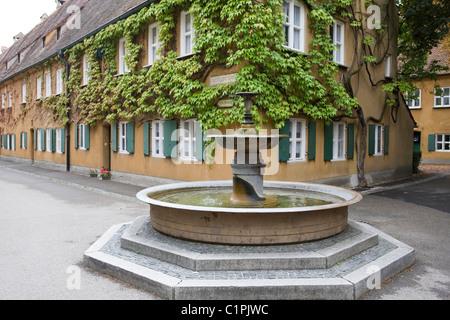 Deutschland, Bayern, Augsburg, Fuggerei, Armenhäuser mit Brunnen im Vordergrund - Stockfoto