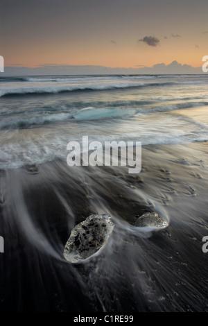 Eisberge am schwarzen Strand mit den Gezeiten waschen um sie herum in Island - Stockfoto