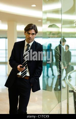 Geschäftsmann Glaswand gelehnt, mit Handy - Stockfoto