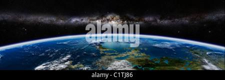 Künstlers Konzept eines außerirdischen Planeten mit einer Galaxie am Horizont. - Stockfoto