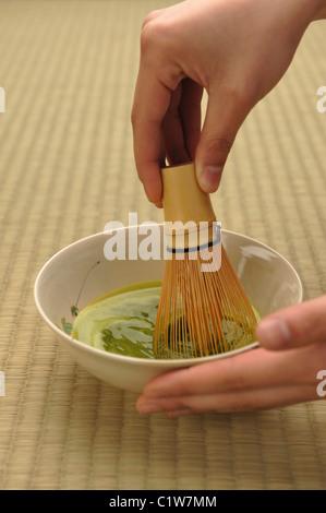 Person mit einem Bambusbesen Matcha Tee vorbereiten - Stockfoto
