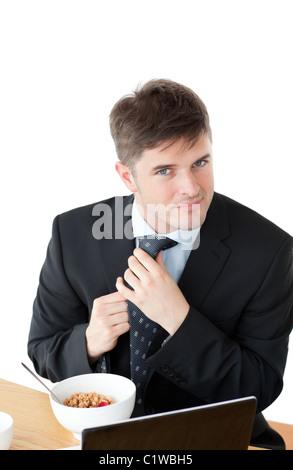 Elegante Geschäftsmann frühstücken und berühren seine Krawatte vor seinem laptop - Stockfoto