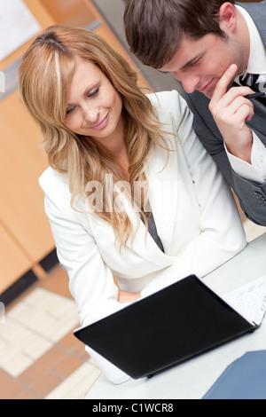 Zwei konzentrierte Geschäftsleute, die an einer Präsentation in ihrem Büro arbeiten - Stockfoto