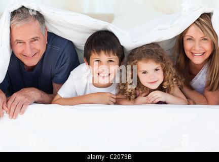Familie in ihrem Schlafzimmer schaut in die Kamera zu Hause - Stockfoto