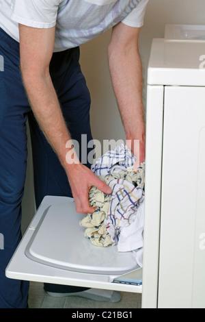 Kleidung in den Trockner laden Mann gekleidet in Freizeitkleidung. Oberkörper und Arme männlichen Erwachsenen laden - Stockfoto