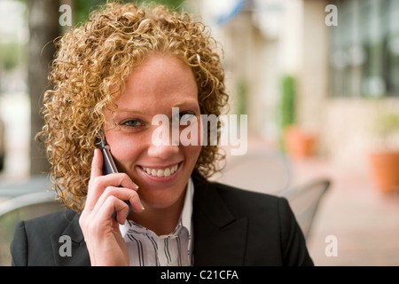 Lächelnde Geschäftsfrau entspannend auf dem Bürgersteig während der Diskussion Geschäft auf ein Handy. - Stockfoto